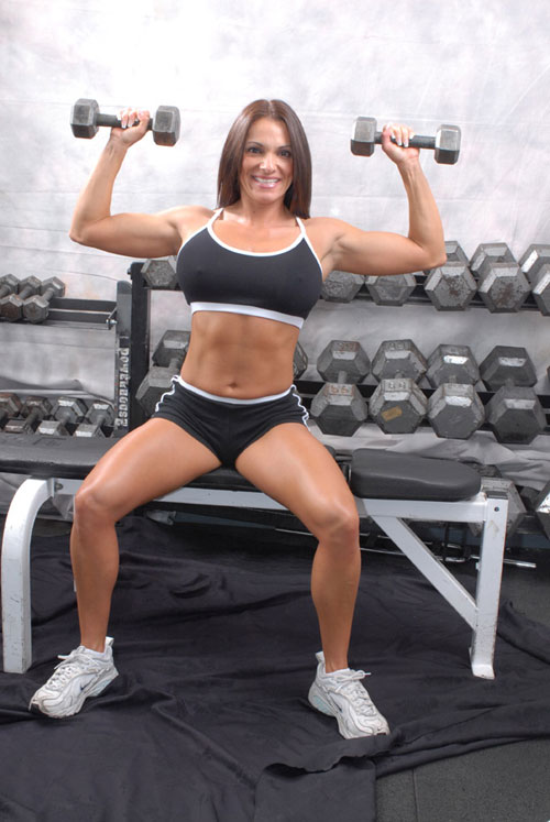 Female bodybuilder Kristine exercises with dumbbells