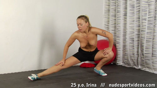 Topless hamstring stretches by a blonde busty gymnast